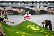Art work by Ackroyd & Harvey made in grass with words by Ben Okri is set to float on the rising tide on the Thames on the 25th of June 2021, Central London, United Kingdom. The message is a call for action to save the planet from climate change catastrophe. Artist Dan Harvey. The art work was moved by activists and laid onto a raft on the Thames as the tide was rising. The event marks the launch of XR Writers Rebel's Paint the Land project, which teams acclaimed writers and artists to create landscape graffitos drawing attention to the climate and ecological emergency. The Speakers at the event included the artist Ackroyd & Harvey, writer Ben Okri, Kelly Hill and Simon Bramwell, co-founder of Extinction Rebellion.  The event finished with a song by Damon Albarn and Mirabella Okra and the Capital Choir.