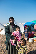 Ragheb Ramadan, age 27, stands with two of his three children at a camp for displaced persons in Atmeh, Syria. The family fled violence in their hometown in Idlib province and now live in the camp full time. Ragheb, however, says he fights for Jabhat al Nusra and so visits here only occasionally to see his family.