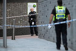 © Licensed to London News Pictures. 10/07/2020. London, UK. Police officers guard a crime scene near Crossharbour DLR station in Poplar. Police were called shortly after 18:00hrs to reports of two males injured at Alexia Square, E14 close to Crossharbour DLR station. Officers attended and found a man, believed aged in his late teens or early 20s, suffering stab injuries. Emergency services provided first aid but despite their efforts, he was pronounced dead at the scene. A second male, believed aged in his late teens, was taken by the LAS to an east London hospital. Photo credit: George Cracknell Wright/LNP