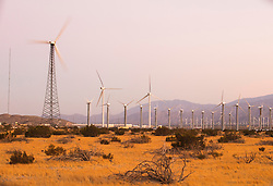 Modern wind turbines at a wind farm in a desert mountain landscape.