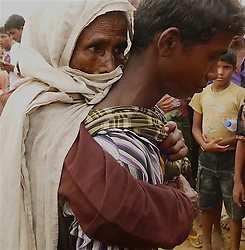 Thousands of Rohingya wait at Balukhali customs field in Bangladesh on September 23, 2017. There is a problem with getting aid to the Rohingya because they are still unsettled in one area. Many Rohingya move around and this is causing NGO's many problems reaching the majority and streamlining a food distribution system . Many Rohingyas have set up small camps along the roads in Coxs Bazar. Also since there is no organized time for the food delivery to come when delivery does come chaos breaks out. This puts many in danger both staff and the Rohingya as people push and shove one another to get to the distribution trucks. Often the trucks leave as the drivers feel their staff are in danger of being harmed by the number of people trying to desperately trying to grab food. NGO staff have often resorted to standing on the roofs of their vehicles to distribute food. Often now small canes are being used to tap people who become disruptive and to get some order to the mayhem of the chaotic food distribution lines. (Photo by Gail Orenstein)