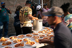 Volunteers from a church serve food for asylum seekers camped at El Chaparral, Tijuana