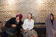 Karin Moen Abercrombie, chef på The Swedish American Museum, sitter på en bänk i muséets utställningslokal bredvid dockor föreställande svenskar som utvandrade till Amerika för ca hundra år sedan. På väggen bakom syns plaketter med namn på svenska utvandrare. Andersonville, Chicago, Illinois, USA<br /> <br /> Foto: Christina Sjögren