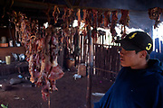 Young Guarani man teenager showing drying meat in a tradtional hut. The Guarani are one of the most populous indigenous populations in Brazil, but with the least amount of land. They mostly live in the State of Mato Grosso do Sul and Mato Grosso. Their tradtional way of life and ancestral land is increasingly at risk from large scale agribusiness and agriculture. There have been recorded cases and allegations of violence between owners of large farms and the Guarani communities in this region.