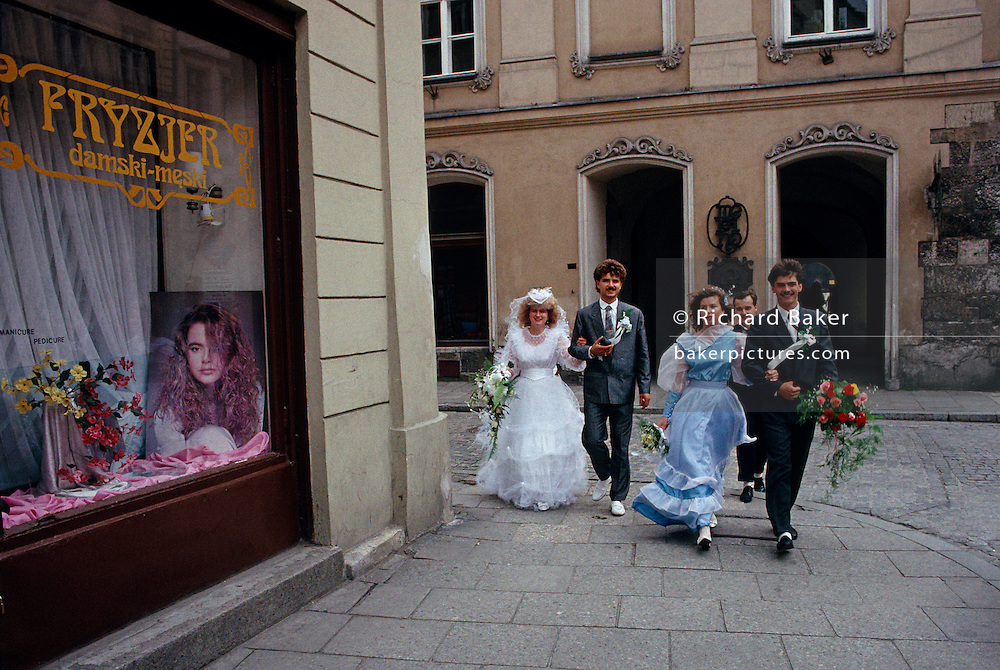 Five friends walk briskly along a street in the southern Polish city of Krakow. One of the ladies is a bride and has either just married the your man whose arm she's holding, or she is hurrying to her wedding ceremony and the friends around her are all on their way to the church. Another girl is probably her bridesmaid, dressed in frilly blue. There are bouquets of fresh flowers and this is a very special day for these young people who are delighted to attend this wedding somewhere in this city where so many atrocities occurred during the second world war. The picture looks dated from the 1980s but it's the summer of 1990, when Poland was about to undergo massive changes economically and culturally. Their clothing looks very east European for that era and are about to stride past a unisex hairdresser's shop window where a model's face stares to the viewer.