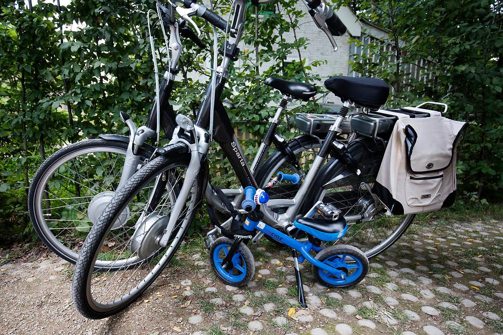 In Austerlitz staat een loopfiets vastgemaakt aan twee elektrische fietsen bij een cafe.<br /> <br /> In Austerlitz a walking bike is locked to two e-bikes near a cafe.