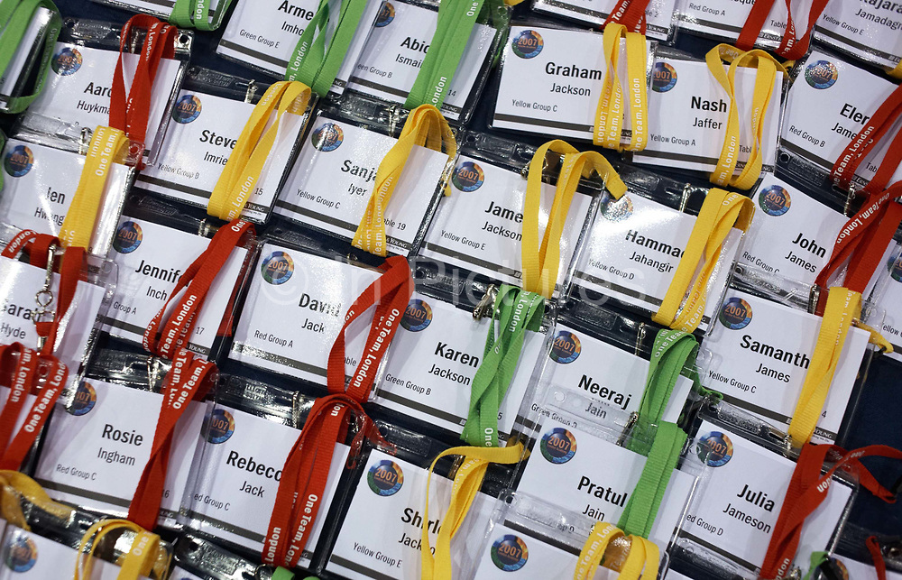 We see a close-up of rows of name badges awaiting collection by their owners at the beginning of an Ernst & Young Academy Day held for 3,000 of company London employees at Excel in London's Docklands, England. Stacked neatly, we see yellow, green and red lanyards wrapped around each individual Christian and surname. Some names yield clues to the peoples' ethnicity: Either White British like Julia and Rosie, British-Asians like Pratul and Neeraj and possibly British-Muslim like Jamal. Each employee will attend this fair where motivational pep-talks from executives, outside speakers and gurus will talk to large groups of E & Y personnel so their presence on this day away from the office is vital for the year's business ahead.