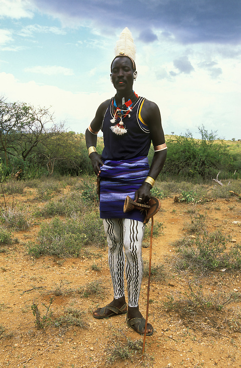 Hamar man with painted legs, ostrich-feather hairdo and a stool in his hand posing for a photograph, in South Omo, Ehtiopia. The 40,000-strong, cattle-herding Hamar are among the largest of the 20 or so ethnic groups which inhabit this culturally diverse region in south-west Ethiopia.