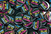 Stand up to racism badges at the No to Trump, No to NATO, Hands off our NHS Demonstration on 3rd December 2019 in London, United Kingdom. Donald Trump is visiting London or the NATO Heads of State summit on the 70th anniversary of the organisation, which the Queen will be hosting a reception for NATO leaders at Buckingham Palace. Meanwhile, there is fear that Boris Johnson and Donald Trump will be in discussion about opening up the NHS to US corporations. Organisers were Together Against Trump which is a collaboration between the Stop Trump Coalition and Stand Up To Trump.