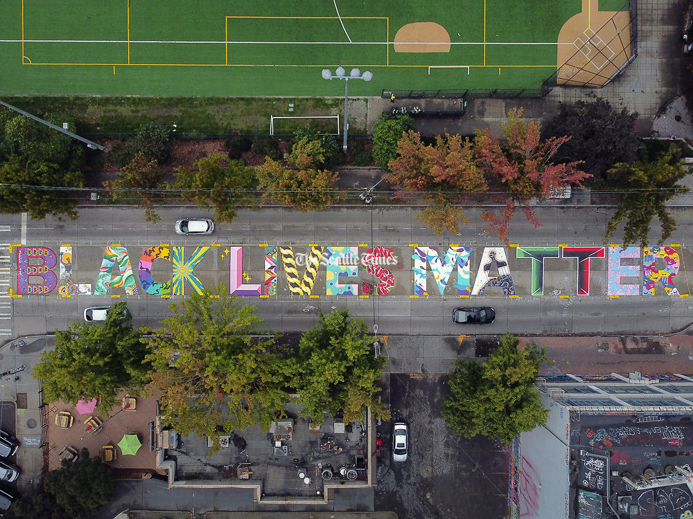 "Traffic moves past the newly repainted ""Black Lives Matter"" mural on Capitol Hill's East Pine Street. (Ken Lambert / The Seattle Times)"