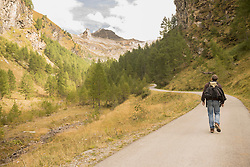 Rear view of mature hiker walking on road, Austrian Alps, Carinthia, Austria