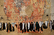 Personal underwaer clothing hangs from string against a wall of peeling plaster, on 21st March 1994, in Lisbon, Portugal.