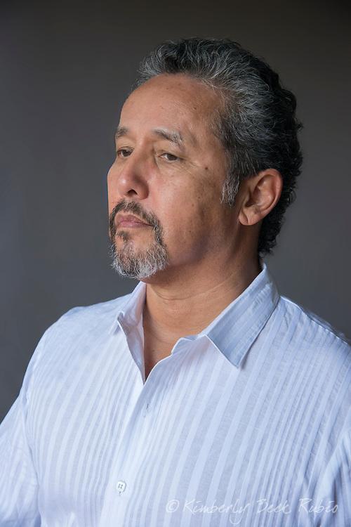 Proud, mature latino man - late 50s, in stylish white button down shirt.