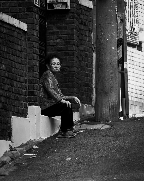 An edlerly lady watches the passersby near Itaewon, Seoul, Korea