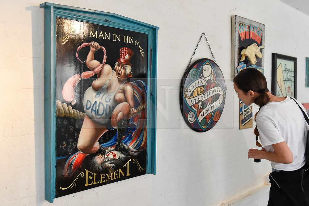 """© Licensed to London News Pictures. 17/08/2018. LONDON, UK. A visitor views a sign depicting Boris Johnson inspired by an 18th century sign painting exhibition at """"Letterheads 2018: London Calling"""", an international gathering of professional sign writers and lettering artists from over 30 countries.  The event is taking place at the Bargehouse, Oxo Tower Wharf in central London untikl 19 August.  Photo credit: Stephen Chung/LNP"""