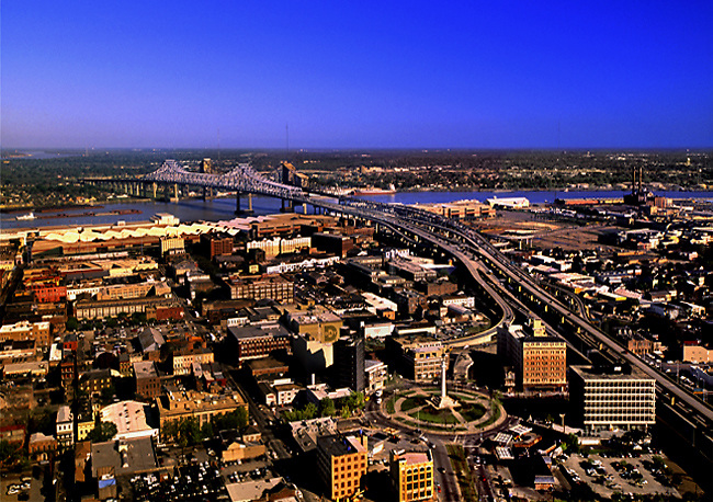 Rooftop view of the CBD and Warehouse Districts, with the Robert E. Lee Circle in the foreground, and the Greater New Orleans Bridge(s) crossing the Mississippi River.