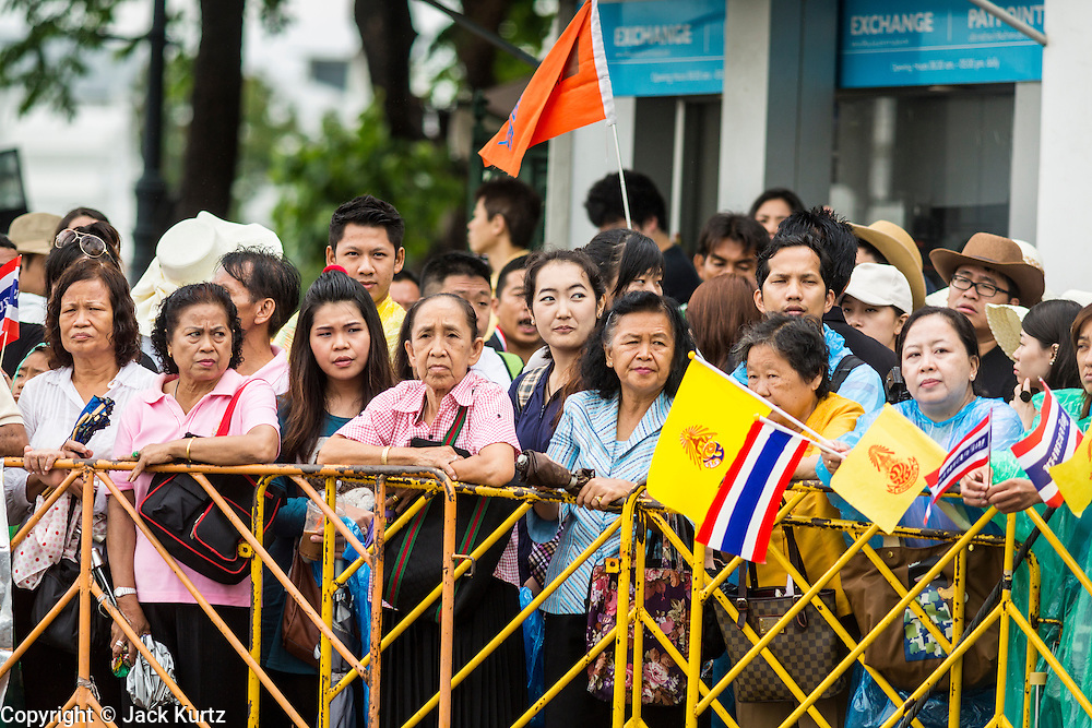 "05 MAY 2013 - BANGKOK, THAILAND:   Thais wait in the rain to see Bhumibol Adulyadej, the King of Thailand, Sunday. The King and Queen, who are both hospitalized and in poor health, did not attend Sunday's event. May 5 marks the 63rd anniversary of the Coronation of His Majesty King Bhumibol Adulyadej. The day is celebrated as a national holiday; since this year it falls on a Sunday, the holiday will be observed on Monday May 6, and as such all government offices and commercial banks will close for the day. HM King Bhumibol Adulyadej is the longest reigning monarch in the world. Each year on the 5th of May, the Kingdom of Thailand commemorates the day when, in 1950, the Coronation Ceremony was held for His Majesty King Bhumibol Adulyadej, the 9th in the Chakri Dynasty (Rama IX). On the 5th of May, His Majesty conducts a merit making ceremony, presenting offerings to Buddhist monks, and leads a ""Wien Thien"" ceremony, walking three times around sacred grounds at the Temple of the Emerald Buddha.    PHOTO BY JACK KURTZ"
