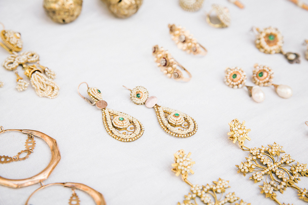 LUCCA, ITALY - 25 OCTOBER 2018: Antique earrings in gold filigree with seed pearls and emerald green stones (Italy, circa 1840) (center, among other Italian 19th century earrings), from Annette Klein's private collection, are shown here in her home in Lucca, Italy, on October 25th 2018.<br /> <br /> Annette Klein, who grew up near Cologne in Germany, graduated with a PhD in the History of Theatre. She is an Art Historian, a collector and researcher of antique earrings. Her current research focuses on antique earrings from the 17th and 18th centuries and their geographical, historical, social and cultural context.