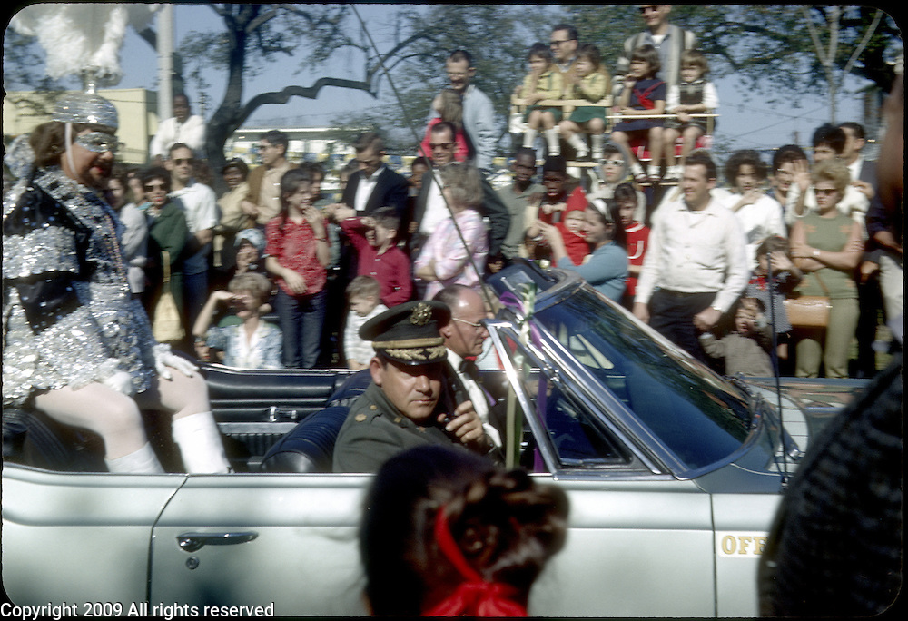 Revelers participate in the 1966 Mardi Gras parade in New Orleans, Louisiana. Men dressed in costumes pass in a gray convertible car.