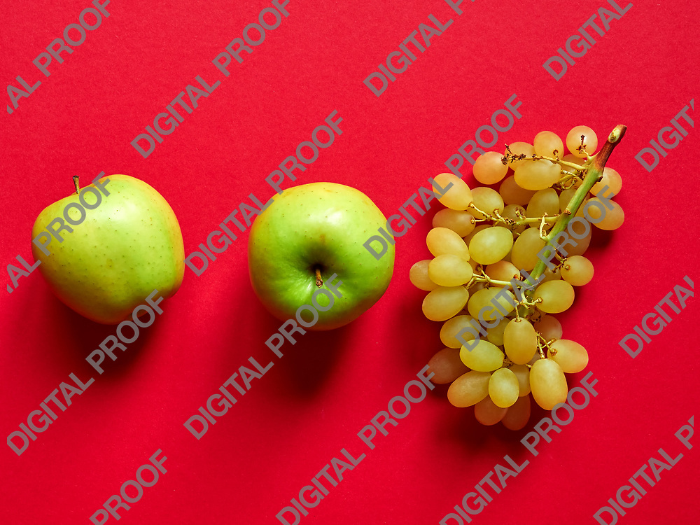 Above view of isolated set of a green apple with a bunch of sweet seedless grapes in studio with red background