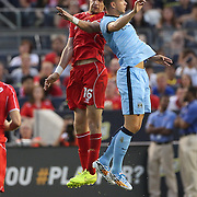 Sebastián Coates, (left), Liverpool and Edin Dzeko, Manchester City, challenge for a header during the Manchester City Vs Liverpool FC Guinness International Champions Cup match at Yankee Stadium, The Bronx, New York, USA. 30th July 2014. Photo Tim Clayton