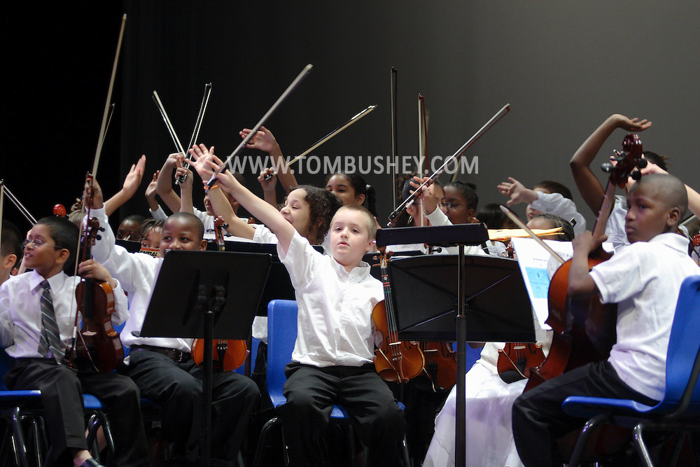 Middletown, NY - Elementary school students wave to their families before the start of a band concert on the stage at Middletown High School on May 28, 2008.