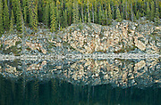 Rocky shoreline reflection in Horseshoe Lake<br /> Jasper National Park<br /> Alberta<br /> Canada