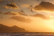 Sunset and clouds over Garn For and Yr Eifl, mountains on the Llyn Peninsula, North Wales. Surf rolls in over the vast shallow beach of Dinas Dinlle in the foreground