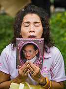 13 OCTOBER 2016 - BANGKOK, THAILAND: A woman holds a portrait of Bhumibol Adulyadej, the King of Thailand, while she prays for him at Siriraj Hospital. Thousands of people came to the hospital to pray for the beloved monarch. Bhumibol Adulyadej, the King of Thailand, died at Siriraj Hospital in Bangkok Thursday, October 13, 2016. Bhumibol Adulyadej, 5 December 1927 – 13 October 2016, was the ninth monarch of Thailand from the Chakri Dynasty and is known as Rama IX. He became King on June 9, 1946 and served as King of Thailand for 70 years, 126 days. He was, at the time of his death, the world's longest-serving head of state and the longest-reigning monarch in Thai history.       PHOTO BY JACK KURTZ