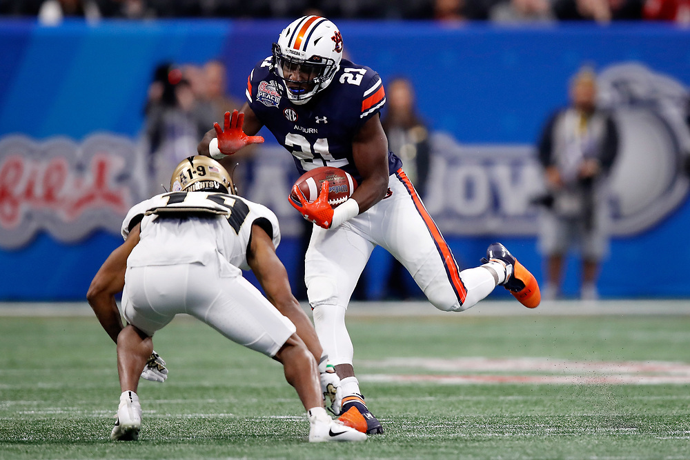 Auburn Tigers running back Kerryon Johnson (21) runs the ball against UCF Knights defensive back Mike Hughes (19) during the 2018 Chick-fil-A Peach Bowl NCAA football game on Monday, January 1, 2018 in Atlanta. (Paul Abell / Abell Images for the Chick-fil-A Peach Bowl)
