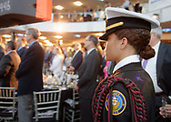 Garden City, New York, U.S. June 6, 2019. At right, a member of the Freeport High School Navy Junior ROTC is one of the cadets standing in front of the stage as Select Chorale members sing during Apollo at 50 Anniversary Dinner, an Apollo astronaut tribute celebrating the Apollo 11 mission Moon landing, at Cradle of Aviation Museum. Her uniform jacket has a braided epaulet on the left shoulder.