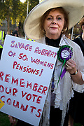 Women born in the 1950s held a Day of Action to draw attention to the women affected by the rise of the state pension age, from 60 to 66, organised by different groups including WASPI Women Against State Pension Inequality Campaign, BackTo60, and We Paid In You Pay Out on October 10th 2018 in London, United Kingdom. An elegant woman wearing a sunhat and rosette holds a placard accusing the government of savage robbery.