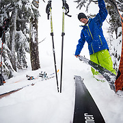 Tyler Hatcher pulls skins In a tree for shelter for another run in the Cascade backcountry during a winter storm.