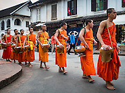 "11 MARCH 2016 - LUANG PRABANG, LAOS:   Buddhist monks walk down the main street of Luang Prabang during the morning tak bat. Luang Prabang was named a UNESCO World Heritage Site in 1995. The move saved the city's colonial architecture but the explosion of mass tourism has taken a toll on the city's soul. According to one recent study, a small plot of land that sold for $8,000 three years ago now goes for $120,000. Many longtime residents are selling their homes and moving to small developments around the city. The old homes are then converted to guesthouses, restaurants and spas. The city is famous for the morning ""tak bat,"" or monks' morning alms rounds. Every morning hundreds of Buddhist monks come out before dawn and walk in a silent procession through the city accepting alms from residents. Now, most of the people presenting alms to the monks are tourists, since so many Lao people have moved outside of the city center. About 50,000 people are thought to live in the Luang Prabang area, the city received more than 530,000 tourists in 2014.     PHOTO BY JACK KURTZ"