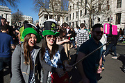 London, UK. Sunday 16th March 2014. Revellers gather in central London for the annual St Patrick's Day celebrations. Saint Patrick's Day or the Feast of Saint Patrick is a cultural and religious holiday celebrated annually on 17 March, the death date of the most commonly-recognised patron saint of Ireland, Saint Patrick. Nowadays the celebration is a fun excuse for some craic and lots of drinking. Two Chinese girls shoot a selfie using a selfie pod.