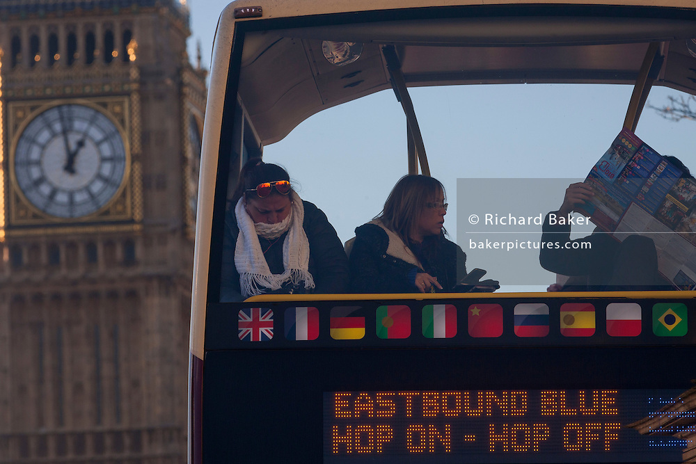 A foreshortened perspective of a tour bus with tourists reading their London map and in the background, the clockface of Elizabeth Tower of the British parliament, on 18th January 2017, in London England.