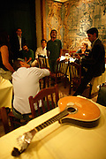 """Camane is one of the most acclaimed singers from the new generation. Here he is participating in an unformal session at restaurant """"Mesa de Frades"""", an old chapel in Alfama typical neighborhood. On the foreground a Portuguese Guitar is placed on a table. It's believed that this twelve-chord instrument is an evolution from arabic citar."""