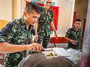"09 AUGUST 2014 - BANGKOK, THAILAND: Thai soldiers plate up chicken stir fried with chilies and basil for people waiting for free food at the Ruby Goddess Shrine in the Dusit section of Bangkok. The seventh month of the Chinese Lunar calendar is called ""Ghost Month"" during which ghosts and spirits, including those of the deceased ancestors, come out from the lower realm. It is common for Chinese people to make merit during the month by burning ""hell money"" and presenting food to the ghosts. At Chinese temples in Thailand, it is also customary to give food to the poorer people in the community.         PHOTO BY JACK KURTZ"