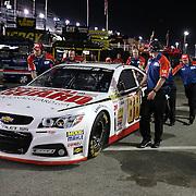 Crew members push the car of driver Dale Earnhardt Jr. during the  56th Annual NASCAR Daytona 500 practice session at Daytona International Speedway on Wednesday, February 19, 2014 in Daytona Beach, Florida.  (AP Photo/Alex Menendez)