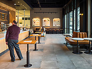 "16 MARCH 2020 - DES MOINES, IOWA:  A customer waits for his beverage in a Starbucks in downtown Des Moines Monday. The Starbucks, like all Starbucks, has put away its chairs and gone to take out only. Sunday night, the Governor announced that the state health department had recorded ""community spread"" in Des Moines. The Iowa Department of Public Health has urged all public buildings, like libraries and schools, to close, and restaurants to switch to take out or delivery only. The State Capitol instituted mitigation measures that included mandatory health screening for everyone going into the building, canceling group tours of the building, and closing the souvenir shop and snack bar.       PHOTO BY JACK KURTZ"