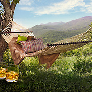 Whiskey bottle and two glasses with a hammock behind and a green mountainous  background behind Ray Massey is an established, award winning, UK professional  photographer, shooting creative advertising and editorial images from his stunning studio in a converted church in Camden Town, London NW1. Ray Massey specialises in drinks and liquids, still life and hands, product, gymnastics, special effects (sfx) and location photography. He is particularly known for dynamic high speed action shots of pours, bubbles, splashes and explosions in beers, champagnes, sodas, cocktails and beverages of all descriptions, as well as perfumes, paint, ink, water – even ice! Ray Massey works throughout the world with advertising agencies, designers, design groups, PR companies and directly with clients. He regularly manages the entire creative process, including post-production composition, manipulation and retouching, working with his team of retouchers to produce final images ready for publication.