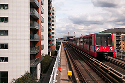 © Licensed to London News Pictures. 23/08/2012, London, UK.  A DLR train runs pass blocks of flat as it arrives at East India station in east London, Thursday, Aug. 23, 2012. DLR, Docklands Light Railway, is celebrates its 25th annivesary today. Photo credit : Sang Tan/LNP