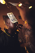 A Nigerian singer is adorned with money from his supporters. Singing and music is outlawed under Sharia Law but exists anway..The implementation of Islamic Sharia Law across the twelve northern states of Nigeria, centres upon Kano, the largest Muslim Husa city, under the feudal, political and economic rule of the Emir of Kano. Islamic Sharia Law is enforced by official state apparatus including military and police, Islamic schools and education, plus various volunteer Militia groups supported financially and politically by the Emir and other business and political bodies. Fanatical Islamic Sharia religious traditions  are enforced by the Hispah Sharia police. Deliquancy is controlled by the Vigilantes volunteer Militia. Activities such as Animist Pagan Voodoo ceremonies, playing music, drinking and gambling, normally outlawed under Sharia law exist as many parts of the rural and urban areas are controlled by local Mafia, ghetto gangs and rural hunters. The fight for control is never ending between the Emir, government forces, the Mafia and independent militias and gangs. This is fueled by rising petrol costs, and that 70% of the population live below the poverty line. Kano, Kano State, Northern Nigeria, Africa