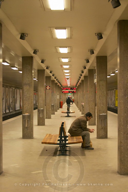 The Stockholm underground subway Tunnelbanan Tunnelbana an empty platform at the station Radmansgatan and concrete pillars a man sitting hunched on a bench with a plastic bag publicity posters on the walls Stockholm, Sweden, Sverige, Europe