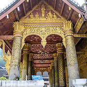 Part of the exterior arches and columns at Wat Mai Suwannaphumaham.  Wat Mai, as it is often known, is a Buddhist temple in Luang Prabang, Laos, located near the Royal Palace Museum. It was built in the 18th century and is one of the most richly decorated Wats in Luang Prabang.