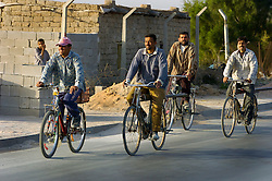 Iraqi Civilians on push bikes cycle through the Basra City as the Iraqi commuter morning rush hour begins passing British Troops who are carrying out an IED sweep in the area. March 2005