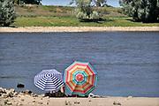 Nederland, nijmegen, 5-8-2020 Vooral jonge mensen zoeken verkoeling aan de oevers van de waal op deze tropisch warme zomerdag . Het is eigenlijk verboden in de rivier te zwemmen vanwege de stroming en het drukke scheepvaartverkeer . Deze strandjes liggen tussen de kribben in de Stadswaard . Foto: ANP/ Hollandse Hoogte/ Flip Franssen