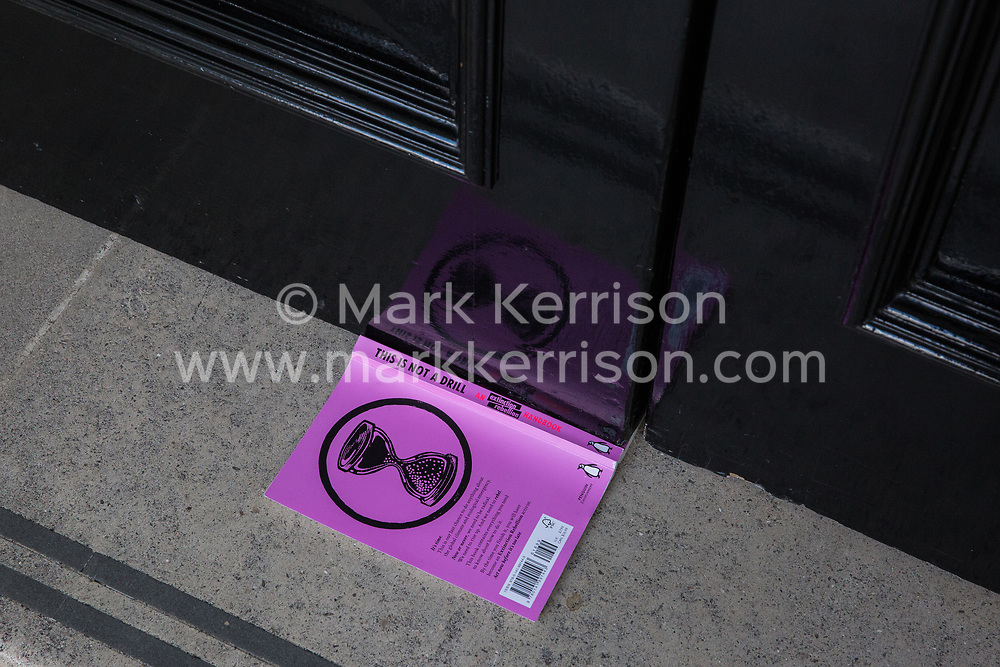 London, UK. 2 July, 2019. A booklet left by climate change activists from Extinction Rebellion Art and Culture outside the offices of Repsol S.A. during a silent procession visiting the offices of five major oil companies - ENI, CNPC, Saudi Aramco, Repsol and BP - to declare them a crime scene.