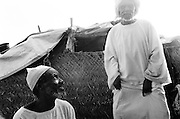 JAACH, SUDAN - JANUARY 11, 2008: Sudanese men outside their home. Located in the southern Darfur region, Jaach is home to many internally displaced Sudanese fleeing conflict.