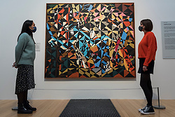 """© Licensed to London News Pictures. 15/10/2020. LONDON, UK.  London, UK. 15 October 2020. Staff members view """"In the Hold"""", c. 1913-14, by David Bomberg. The work is part of new displays in Tate Britain's three collection routes: Rothko and Turner (a new route to celebrate 50 years since Mark Rothko first gave Tate his iconic Seagram Murals to join paintings he so admired by JMW Turner), British Art 1540-1920 and British Art 1930-Now.  Visitors may book online for free to visit the museum.  Photo credit: Stephen Chung/LNP"""
